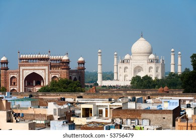 The front facade pure white marble of the Taj Mahal from a far telephoto distance and foreground taj ganj neighborhood rooftops and slums in Agra, India. Horizontal copy space