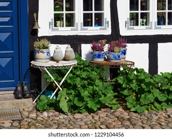 In front facade of a traditional country style Danish house with flowers, pots and garden tables Denmark