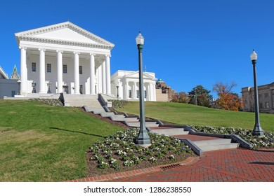 Front facade and walkway to the neoclassical style Virginia State Capitol building in Richmond against a bright blue sky