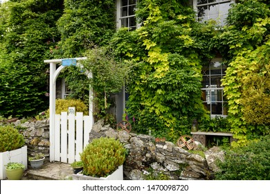 Front garden and gate of Tubbs Mill House bed and breakfast covered in greenery at Mevagissey, Cornwall, England - June 11, 2019