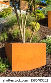 Front garden with modern plant pots made of rusted Corten steel