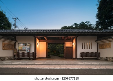 Front gate in longhouse-style of Mejiro Garden with white lacquered walls. This style named nagaya-mon was common in old Edo. Roofed walls made from mud and clay stand on either side