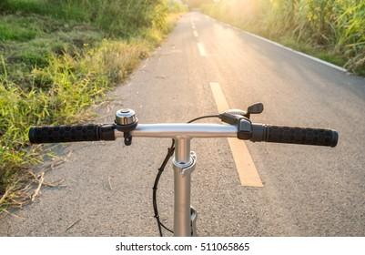 Front handle bar stem biking on rural road at sunset