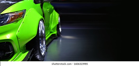 Front headlights of green modify car on black background,copy space