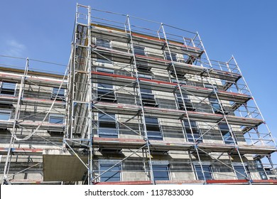 Front of a high-rise building covered in scaffolding in a concept of construction, maintenance or development looking up against a blue sky