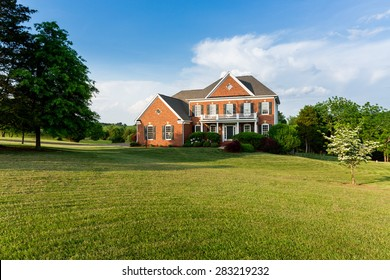 Front of home and garage of large single family modern US house with landscaped gardens and lawn on a warm sunny summers day