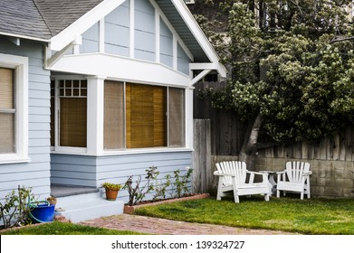 front of a house showing green grass and two chairs