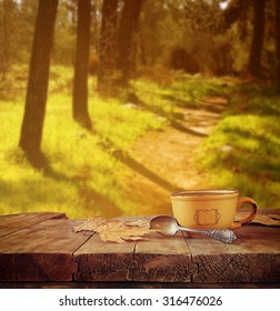 front image of coffee cup over wooden table and autumn leaves in front of autumnal forest background
