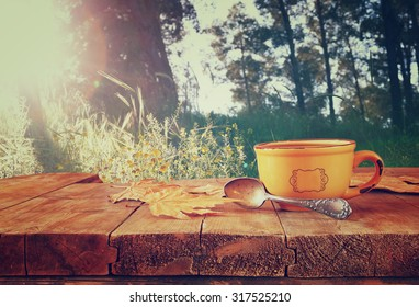 front image of coffee cup over wooden table and autumn leaves in front of forest background . retro style image