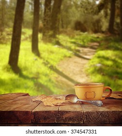 front image of coffee cup over wooden table in front of forest background