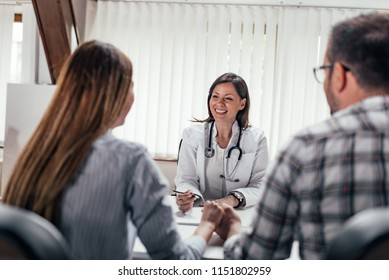 Front image of female doctor having a consultation with a couple.
