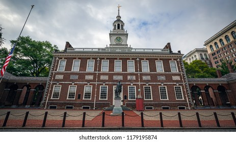 The front of Independence Hall in Philadelphia, PA on a cloudy summer day with the American flag at half staff.