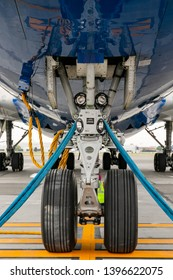 The front landing gear of the aircraft standing on the refueling at the airport.