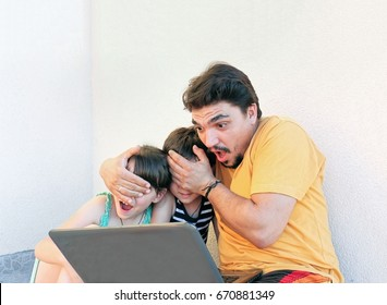 In front of lap top father covering kids eyes not to view inappropriate content on the Internet. Father makes silly face