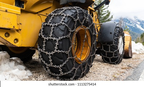Front loader for snow removal with metal snow chains on wheels. Snow removal in the mountains