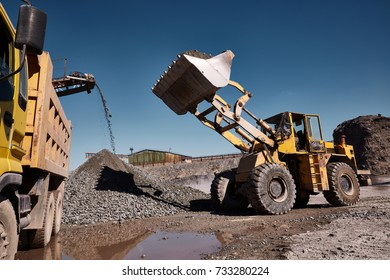 Front loading excavator works in a hot outdoors slag dump. Heavy industrial metallurgical foggy landscape with working conveyor belt on background