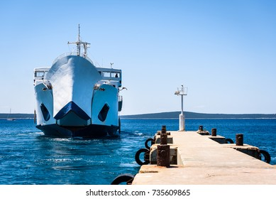 Front loading ferry boat moored with lifted bow at pier. Big ferry boat Lastovo is mooring in island Silba Croatia. Sunny day and blue Adriatic sea.