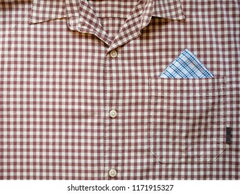 front look of plaid checkered man formal dress shirt with corner of handkerchief look out of chest pocket, close up pattern shot. mans fashion