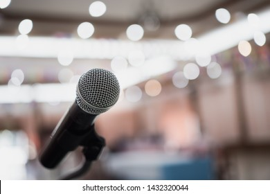 Front Microphone on abstract conference hall prepare for speaker on stage in seminar room, Business meeting and education in teaching classroom or Event light convention hall Background.