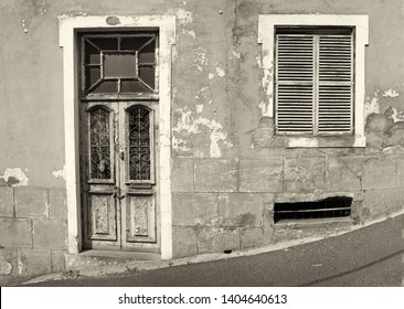 the front of an old abandoned house with shuttered windows and locked wooden door with flaking peeling paint on a sloping street monochrome image