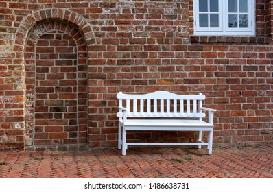 In front of an old brick church stands a small wooden bench, painted white.