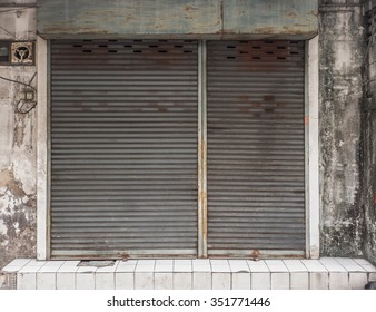 In front of old building with a rusty roller shutter door