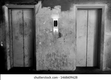 In front of the old elevator door in an abandoned building.