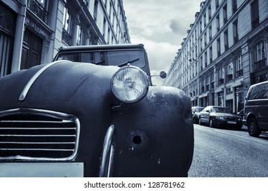The front of an old run-down car (Citroen 2CV) in a little street in Paris, France.