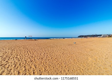 A front on face view of the the sand, sea and blue sky of Durban beach front