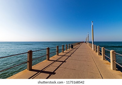 A front on view of a concrete pier leading into the big blue ocean