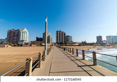 A front on view of the middle of the concrete pier leading off the beach towards the buildings of Durabn