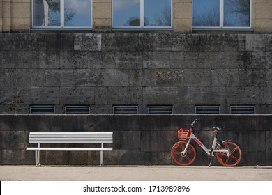 Front parallel outdoor view of white bench and bicycle in front of modern granite stone facade with rectangular windows.