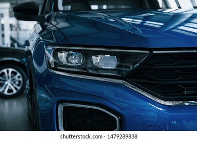 Front part of brand new modern blue car. Parked at showroom. Reflection in the headlights.