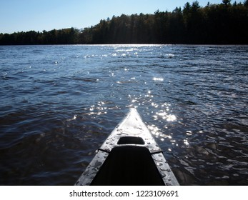 Front part of a kayak in the middle of the river on a sunny fall day. Forest in the background. Taken in October while kayaking in the Upper Wisconsin Dells (Wisconsin, USA).