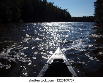 Front part of a kayak moving forward in the river. Forest on both sides, foam on the water, beautiful day with blue sky and no clouds. Taken while kayaking in the Upper Wisconsin Dells (USA).