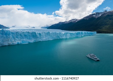 Front part of the Perito Moreno Glacier located in the Southern Patagonian Ice Field and touristic, day trip boat on the turquoise Lago Argentino. Argentina