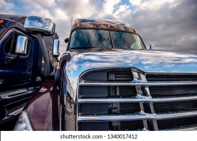 Front part of two professional commercial industrial delivery big rig long haul shiny semi trucks with chrome grilles and mirror and reflection standing side by side on the parking lot in cloudy day