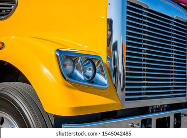Front part of yellow professional big rig industrial powerful bonnet semi truck with chrome grille and bumper and headlight with reflection of sunlight stand-ing on the parking lit