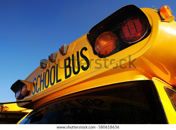 Front part of yellow school bus children educational transport with signs in the parking lot waiting to be in service. Close up photo of school bus in sunny day with clean blue background.