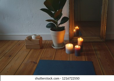 Front part of yoga mat in apartment on wooden floor, with candles, miror, yoga blocks, plant in the background. No people, cosy atmosphere