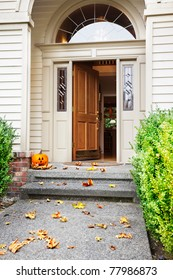 Front path, steps and open front door with fall leaves and jack-o-lantern