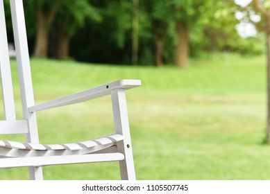 Front patio, garden lawn with classic white old rocking chair. Summer vibes on home porch.