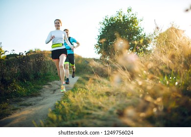 Front photo of sporty woman and man running through park