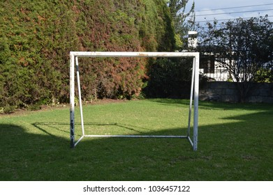 front photograph of a white metallic soccer goal sitting in a fresh green grass outside during a summer day