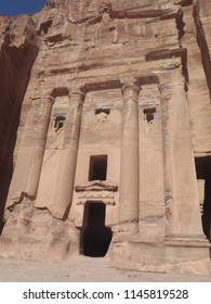 Front porch of an antique building carved in sandstone with visible colums and open doors and windows in Petra - Jordan