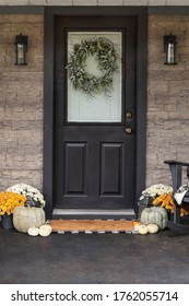 Front porch decorated for Thanksgiving Day with homemade wreath hanging on door. Heirloom gourds,  white pumpkins, and mums giving an inviting atmosphere.