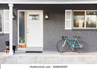 Front porch of grey gray brick house with parked bike
