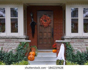 Front porch of house with Halloween decorations and wreath on wooden front door