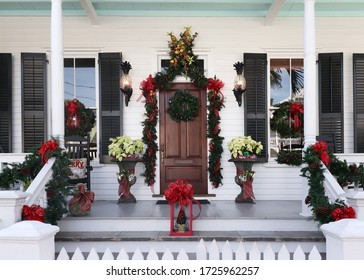 Front porch of a Key West style home in Florida decorated in holiday wreaths and bows for Christmas - Shutterstock ID 1725962257