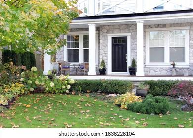 Vordere Veranda eines Luxuswohnheims in Kanada. Vorgarten eines schönen neuen Hauses im Herbst. Herbstlaub im Garten.